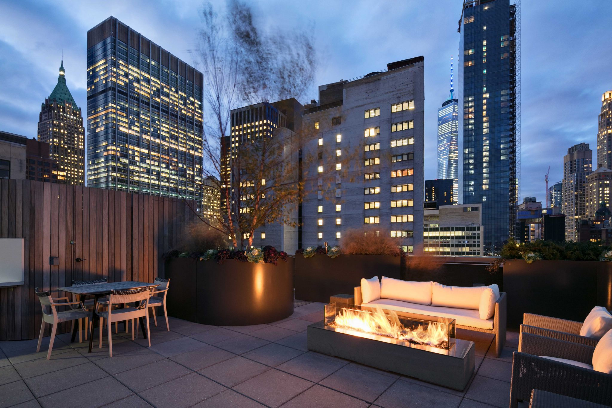 Exterior of rooftop with fire pit, couch and dining table with other downtown New York buildings in background
