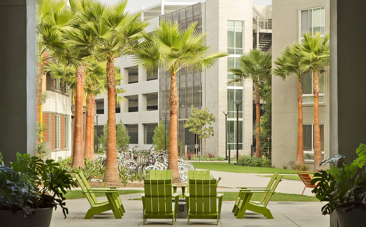 Exterior of apartment building courtyard with adirondack chairs, bikes in a bike rack and palm trees.