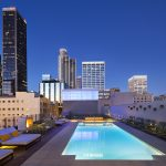 Rooftop pool exterior with chaise lounges and downtown Los Angeles buildings in background.