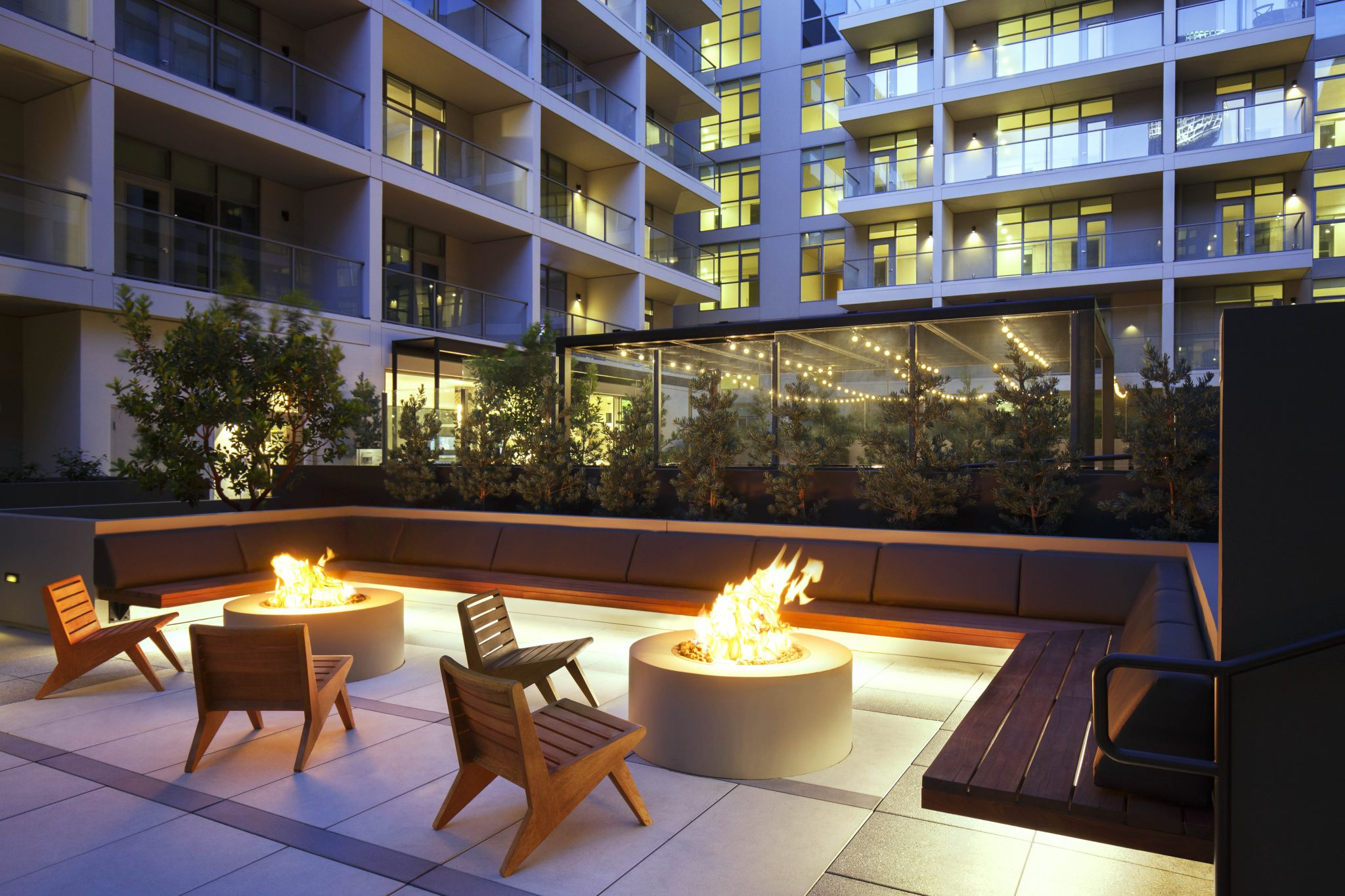 Outdoor seating area with two fire pits and apartment building in background.