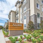 Street-level exterior of Alder sign with apartment building to right and tree-lined street to the left