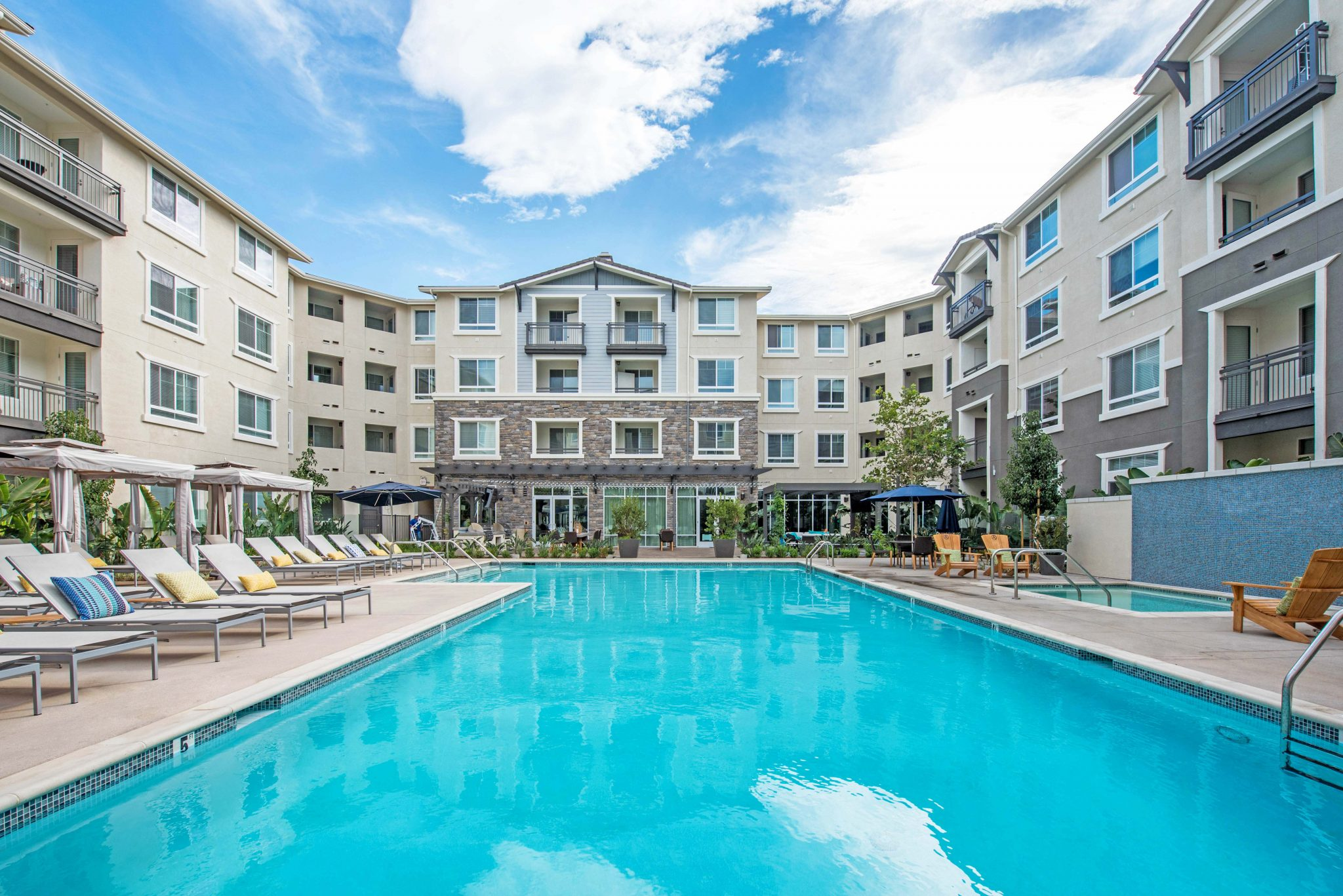 Exterior of apartment complex courtyard with pool, spa, lounge chairs and cabanas.