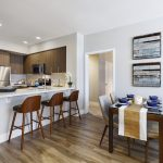Apartment interior with open-plan kitchen, bar-height seating and dining table