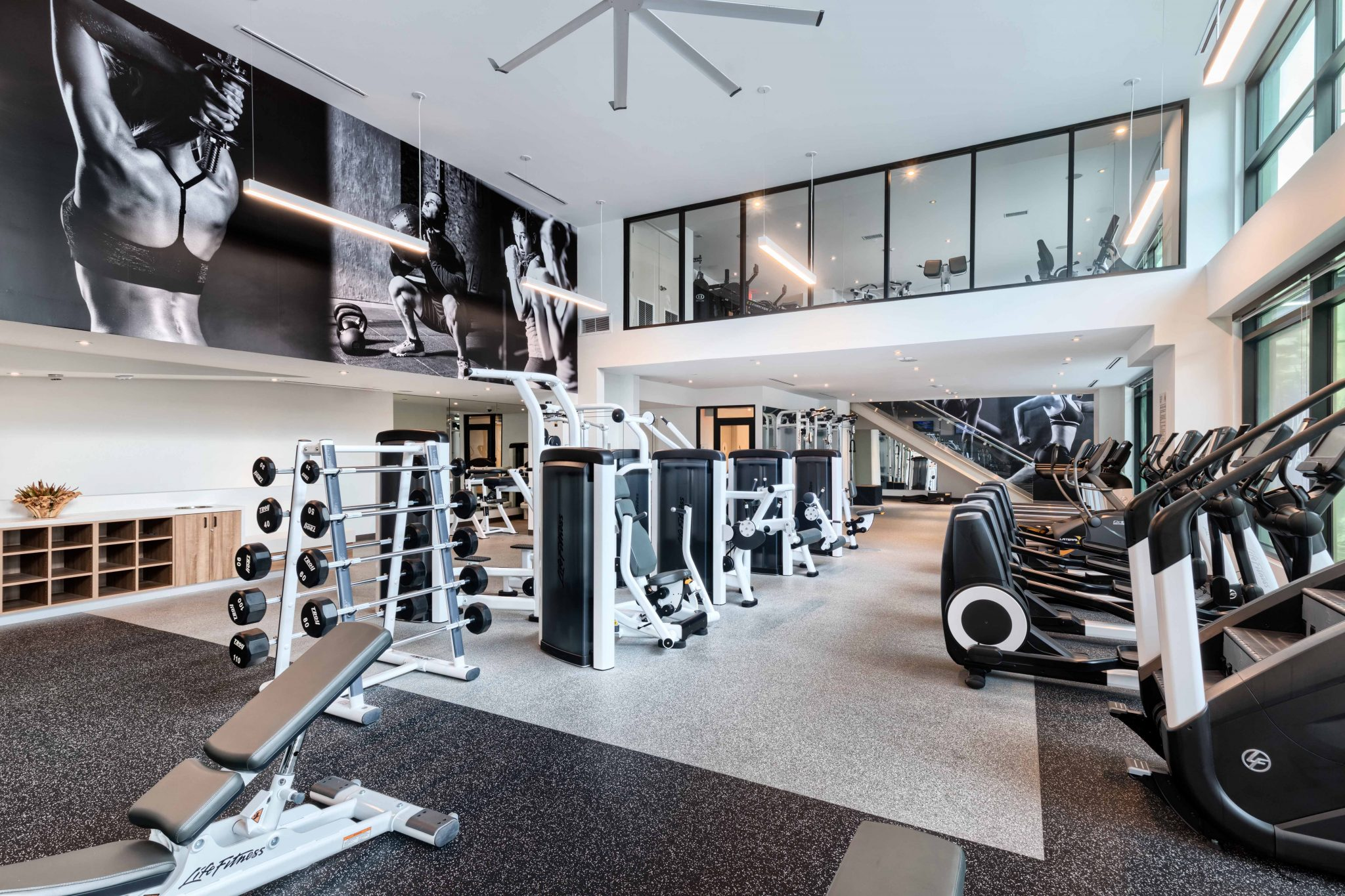 Interior of fitness center with free weights, exercise machines and high ceilings