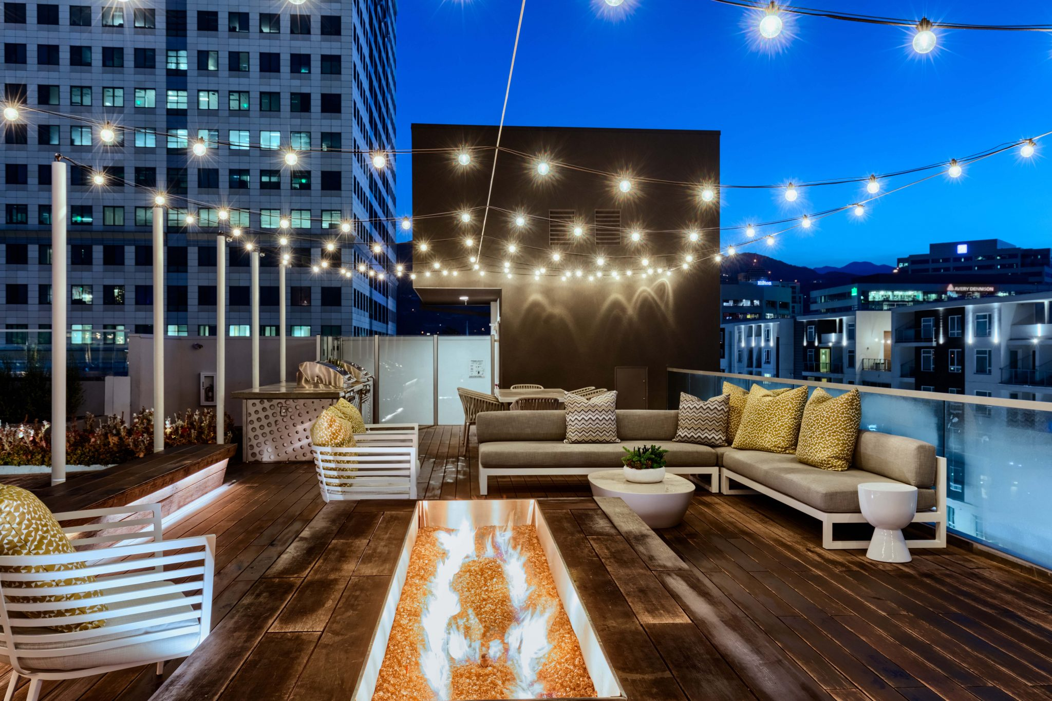 Exterior of rooftop seating area with fire pit and cafe lights overhead