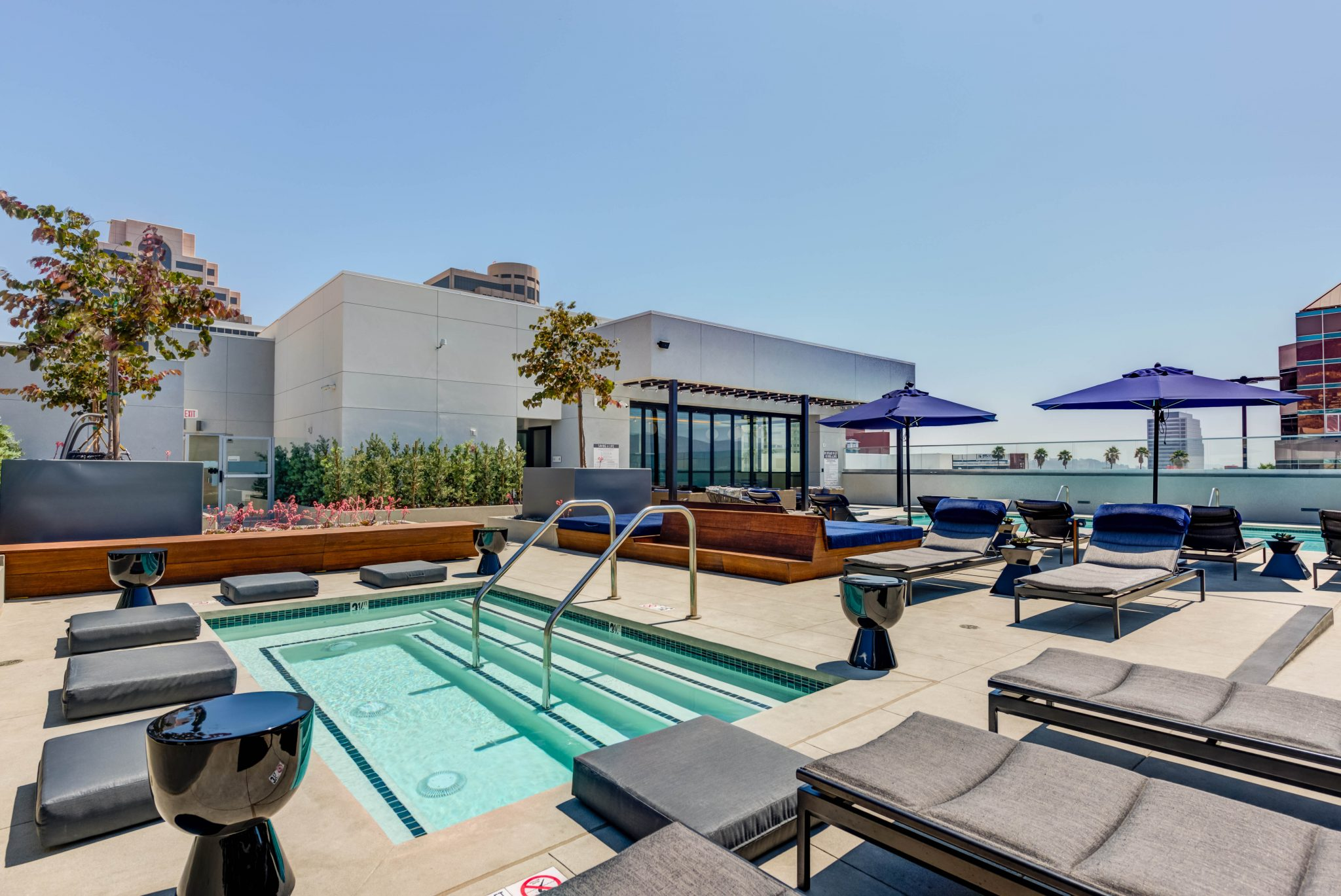 Exterior of rooftop spa surrounded by lounges, seating pads, and wooden benches
