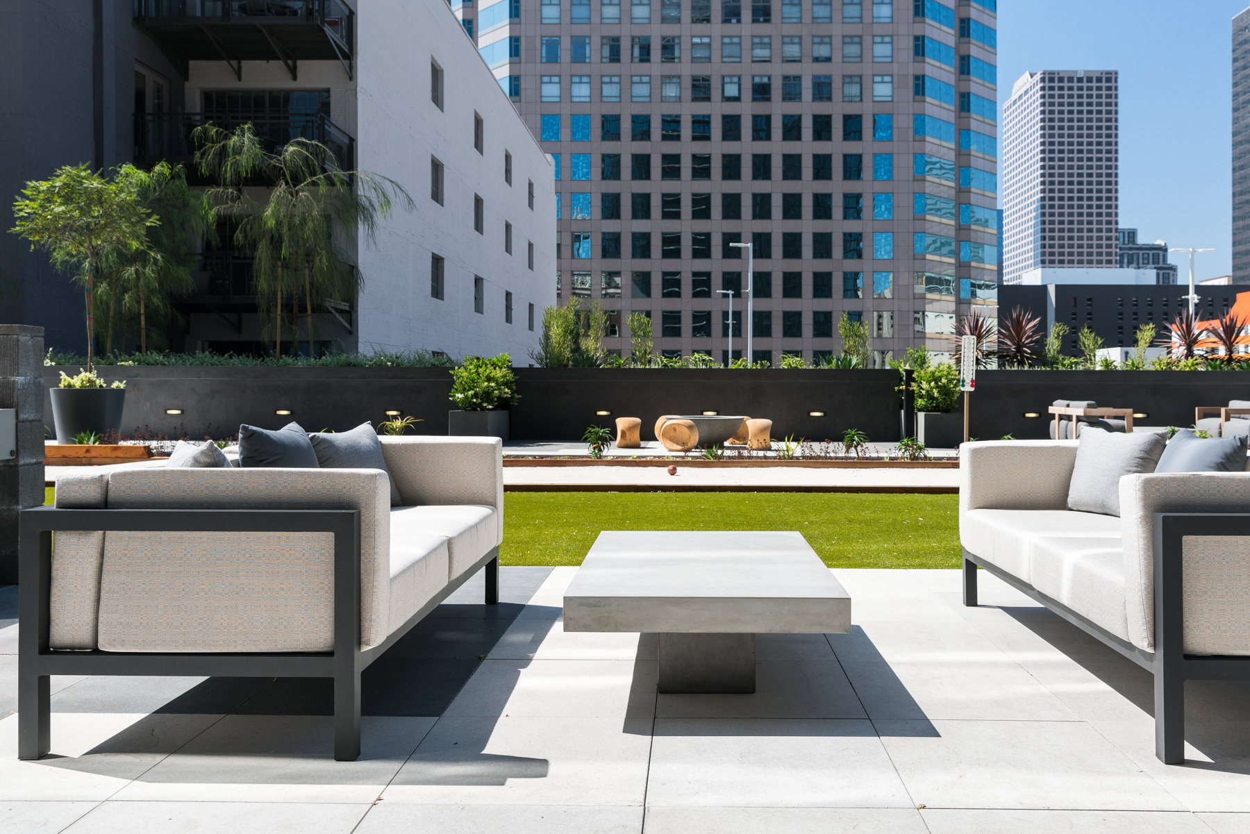 Exterior of rooftop seating area with modern couches and grass in the background