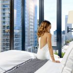 Well-dressed woman sitting on edge of bed in modern apartment with downtown Los Angeles outside the window