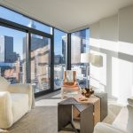 Interior of brightly lit, modern apartment with city views out floor-to-ceiling windows