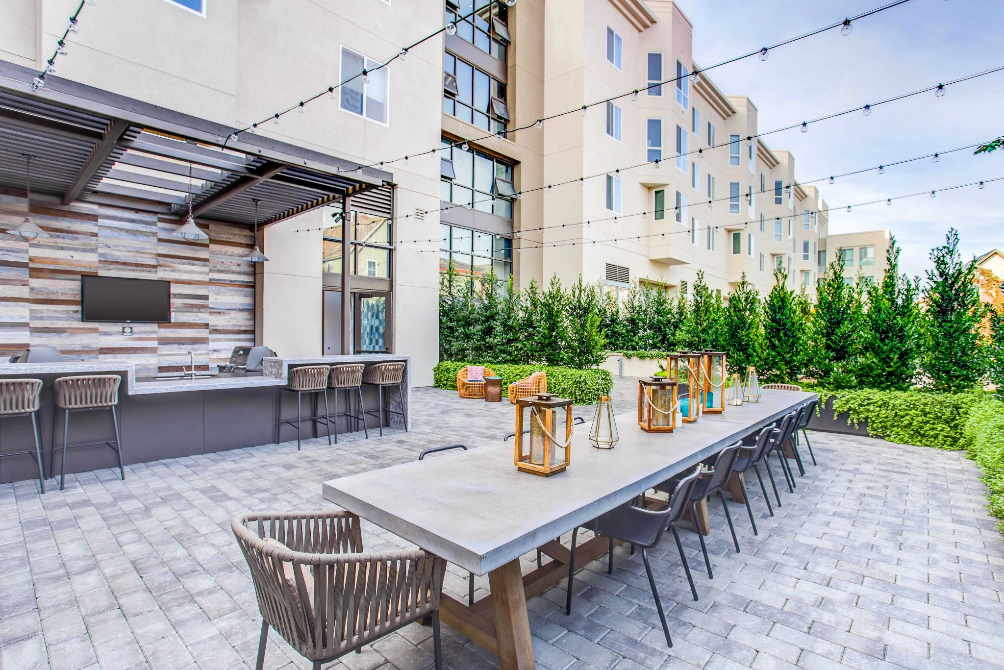 Exterior of apartment complex outdoor courtyard with long dining table and barbeque area