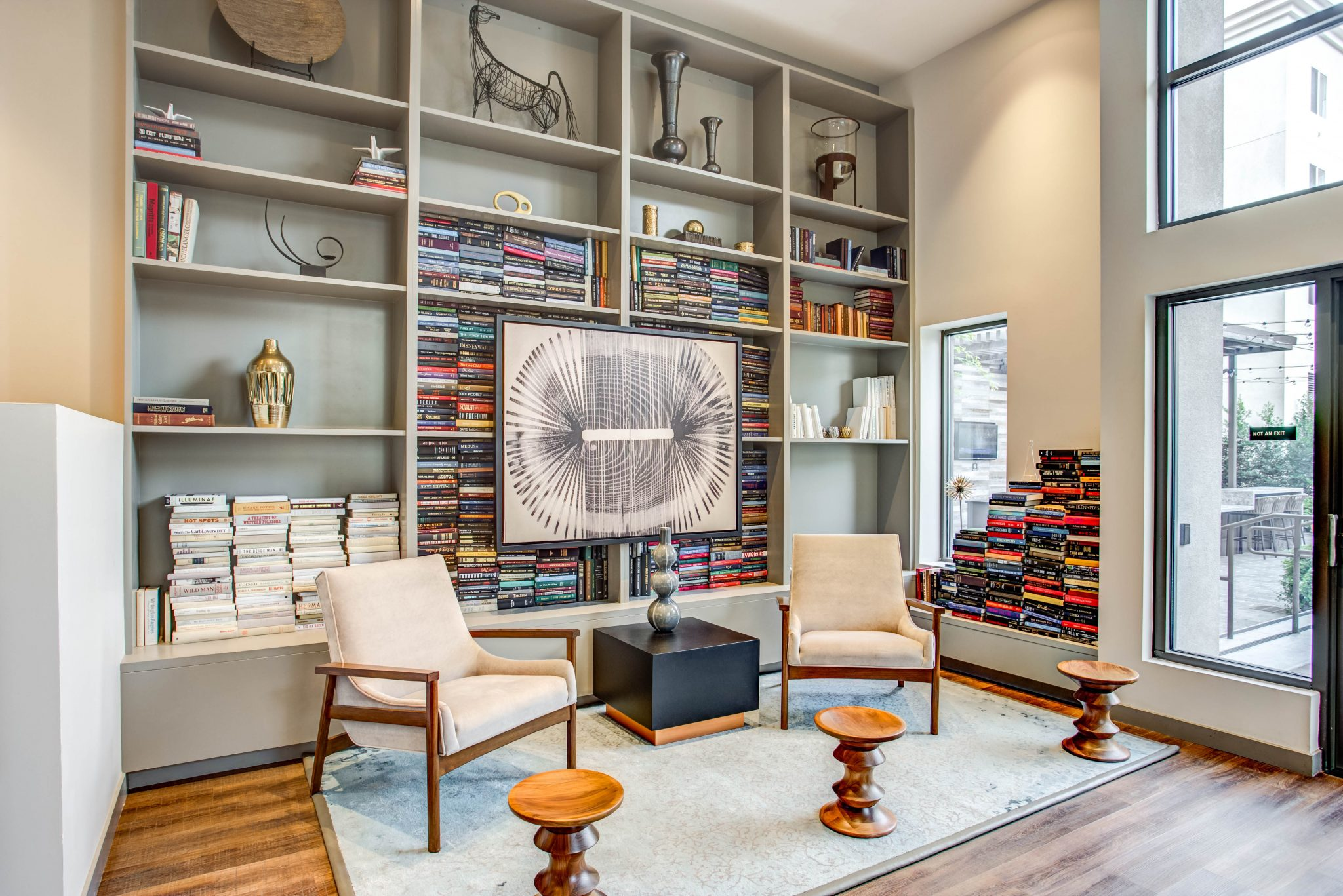 Common-area room with high ceilings, bookshelves and two modern chairs