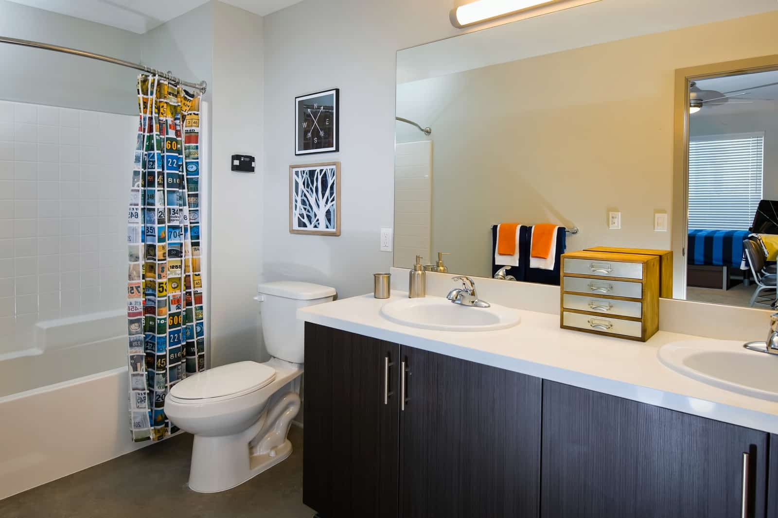 Interior of bathroom with shower over tub, toilet and double vanity.