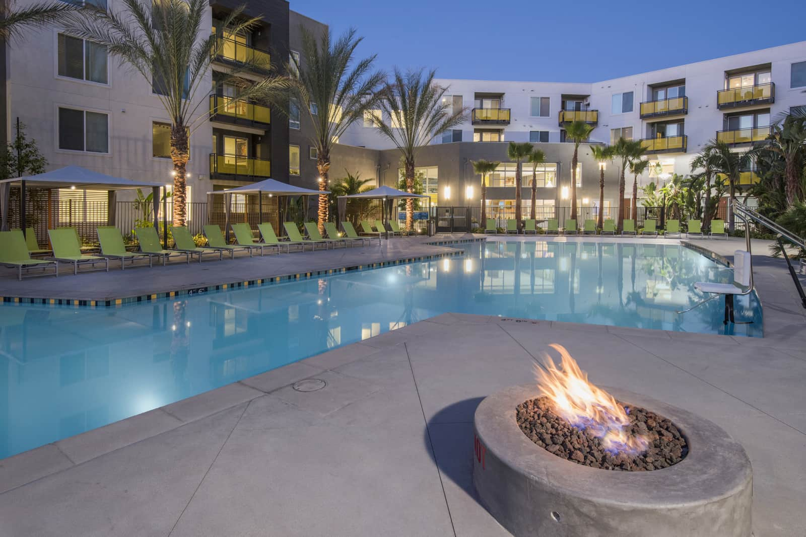 Exterior of courtyard pool at night with chairs, umbrellas, palm trees and a fire pit in the foreground.