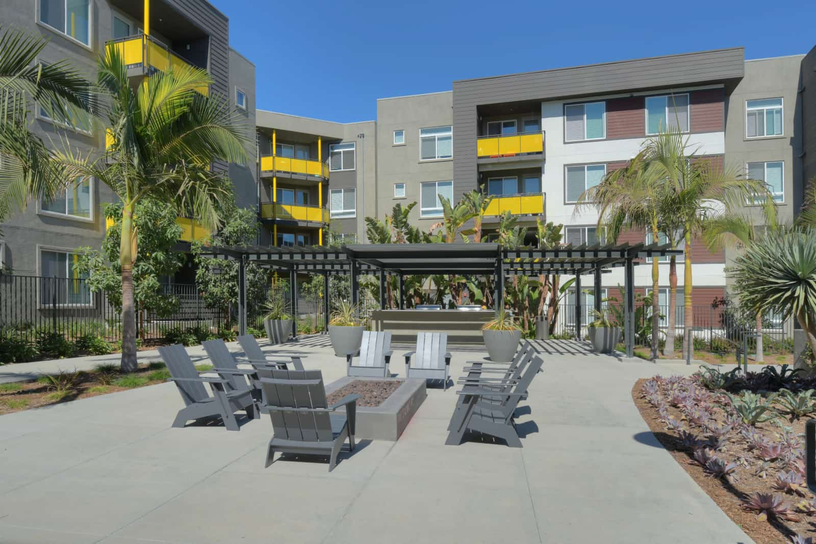 Exterior of apartment building courtyard with adirondack chairs, fire pit and gazebo in the background.