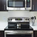 Stainless steel microwave and oven, electric cooktop in kitchen with white counter tops and dark cabinets.