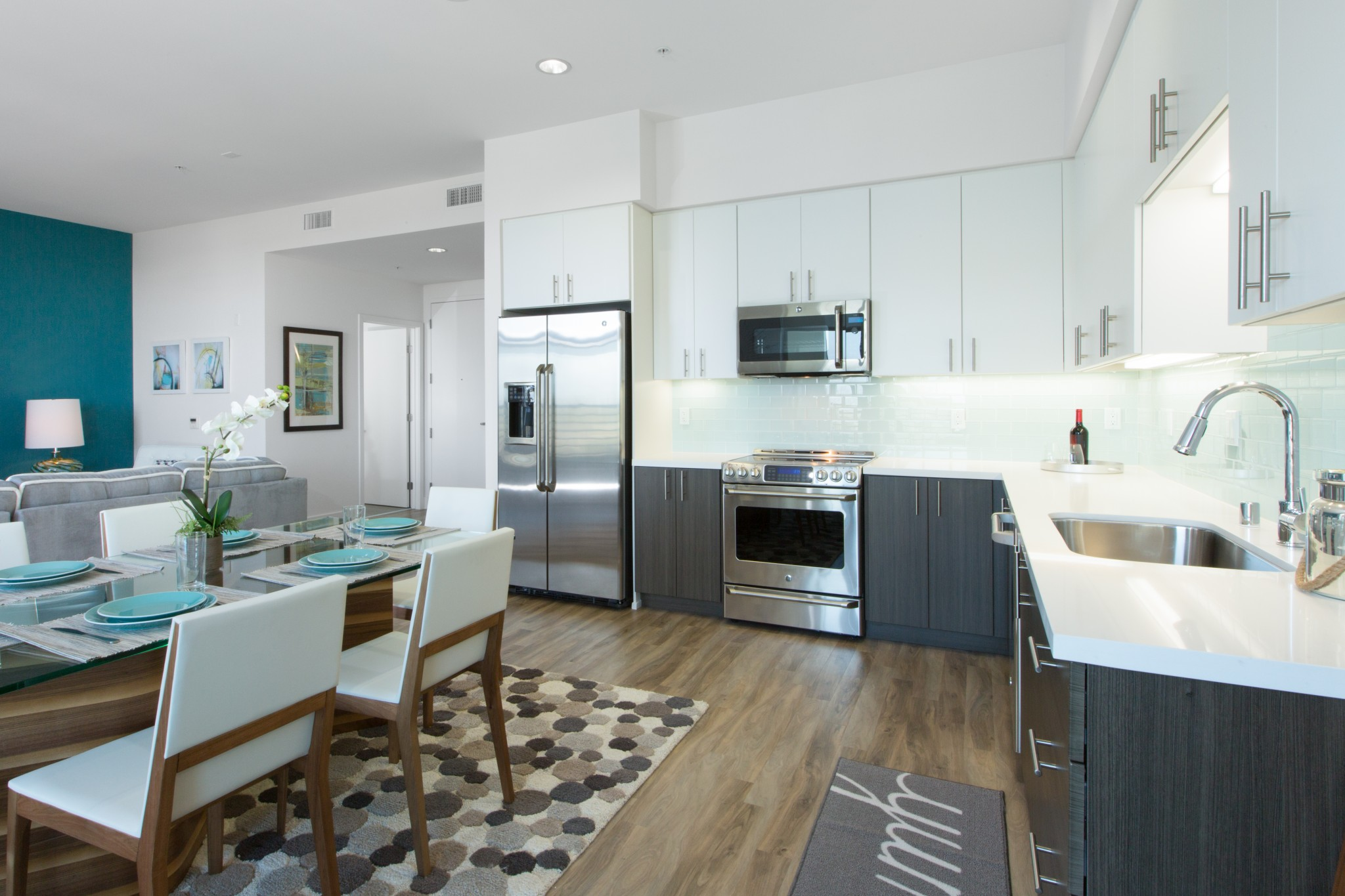 Modern kitchen with stainless steel appliances and view of the living room and a dining table to the right.