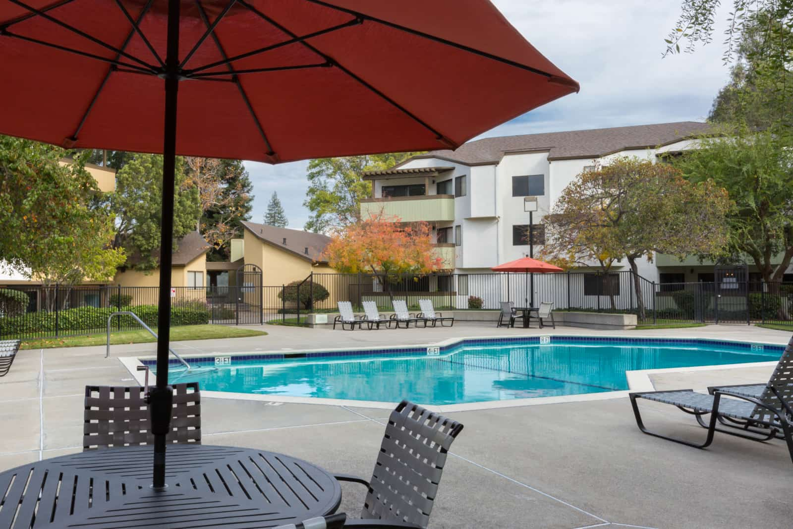 Exterior of pool with table and umbrella in foreground with 3-story apartment buildings in back ground.