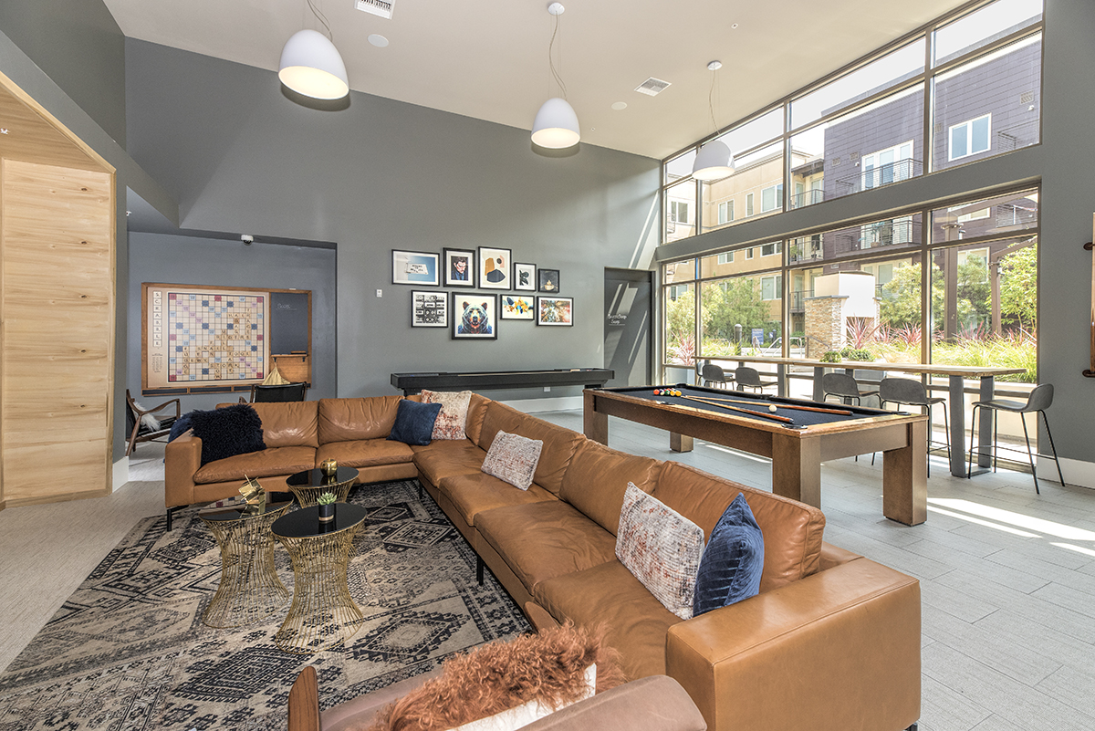 Interior of common area with couch, coffee tables, shuffleboard and pool table.