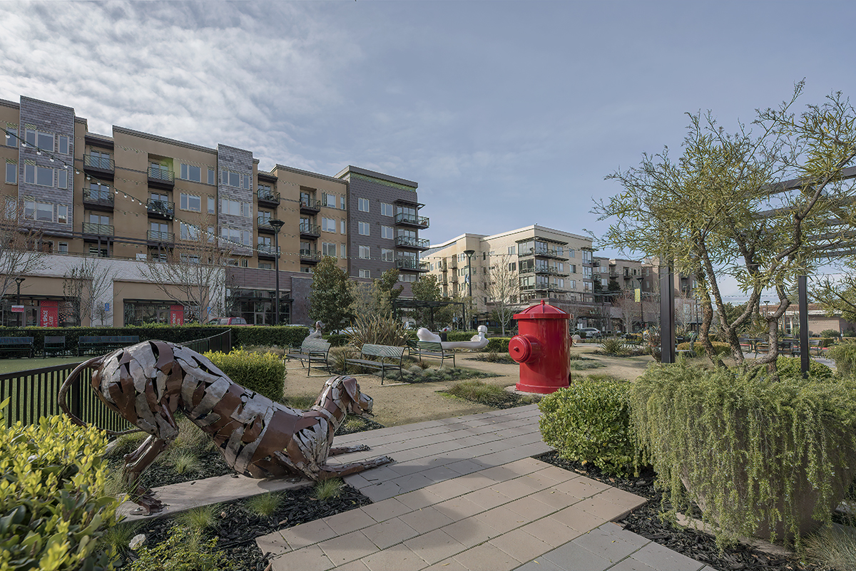 View of the apartment building with metal dog and hydrant sculptures in the foreground.