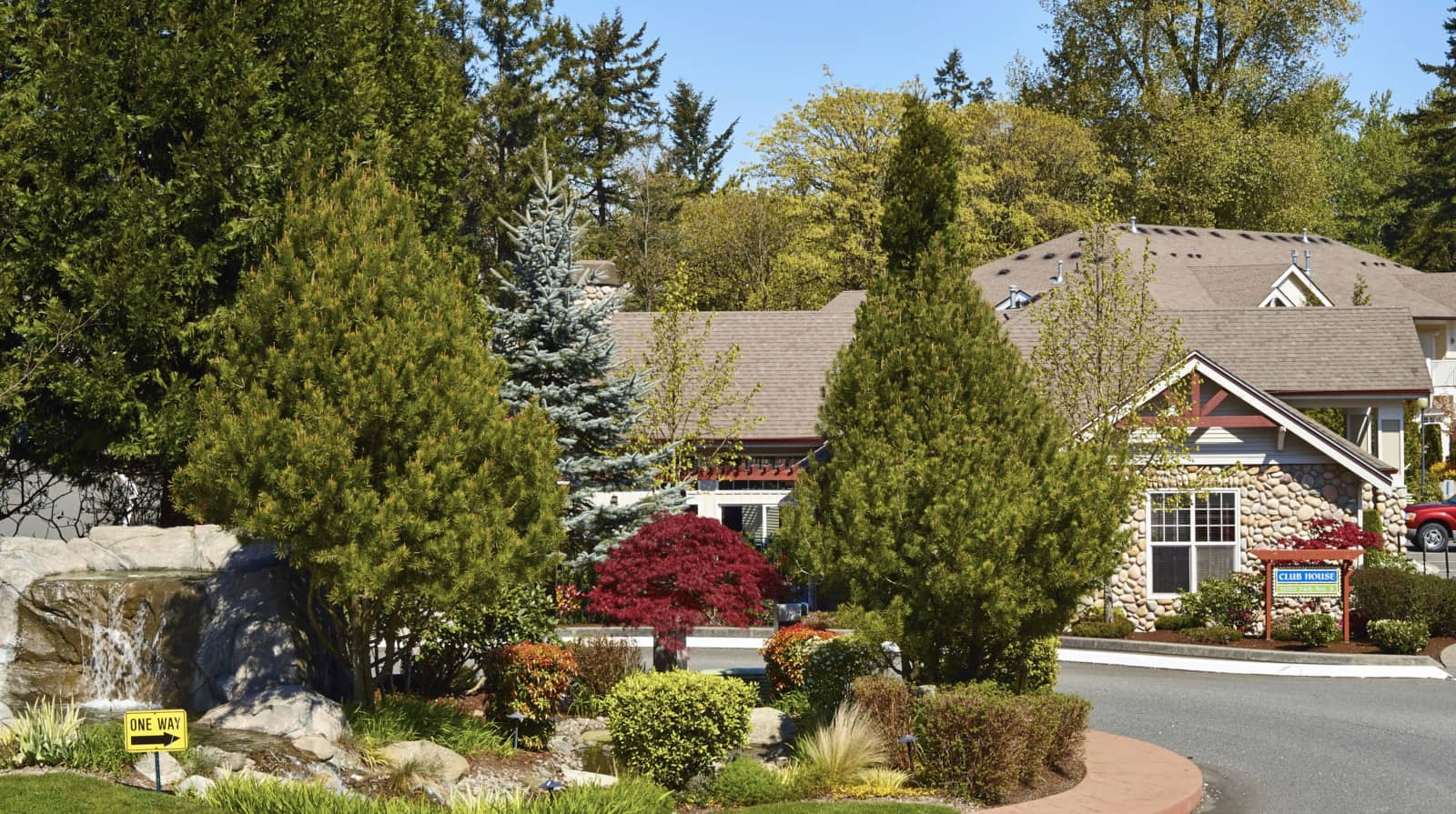 View of the the club house from across the street with pine trees in the foreground.