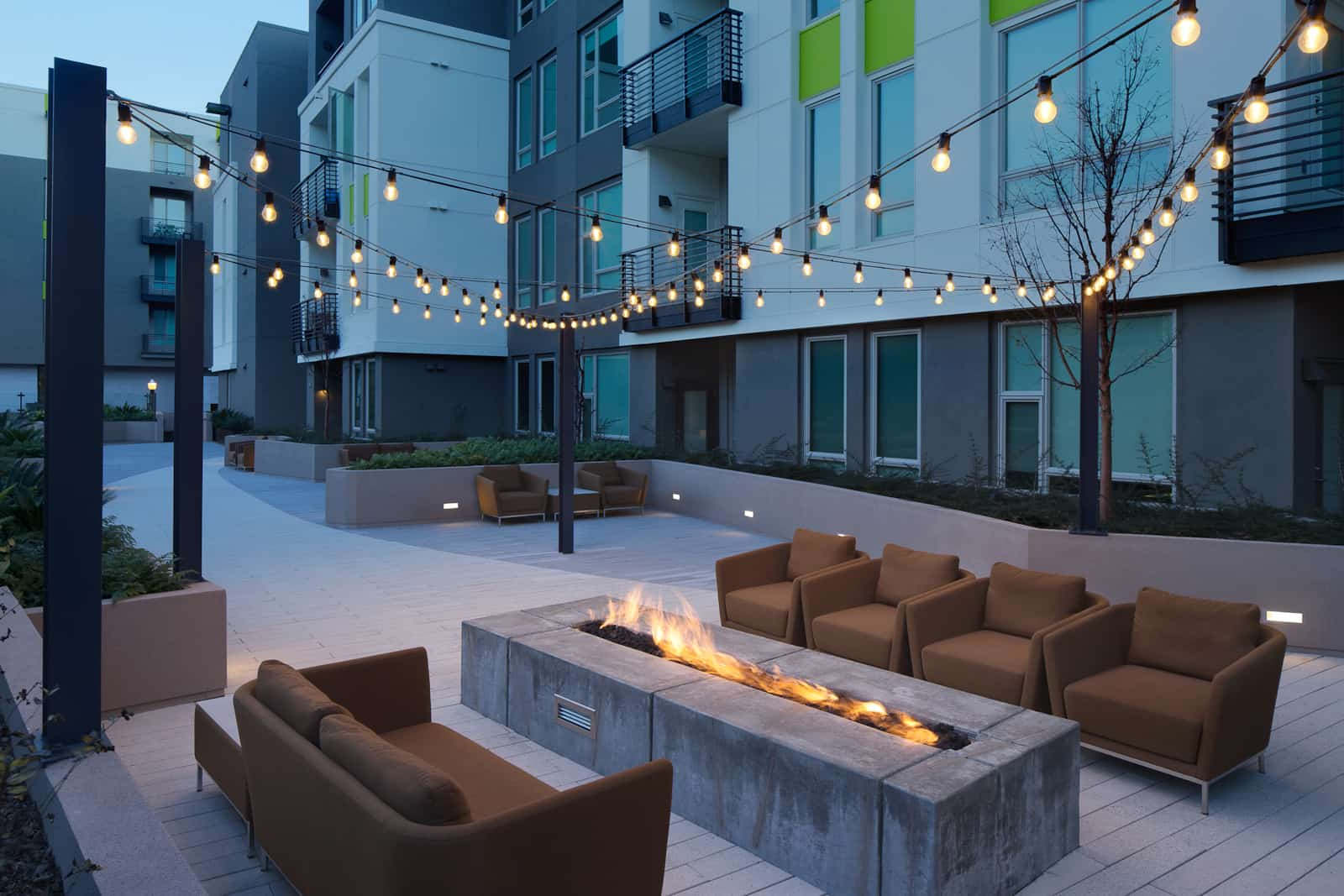 Exterior of firepit and outdoor chairs with string lights above at dusk.