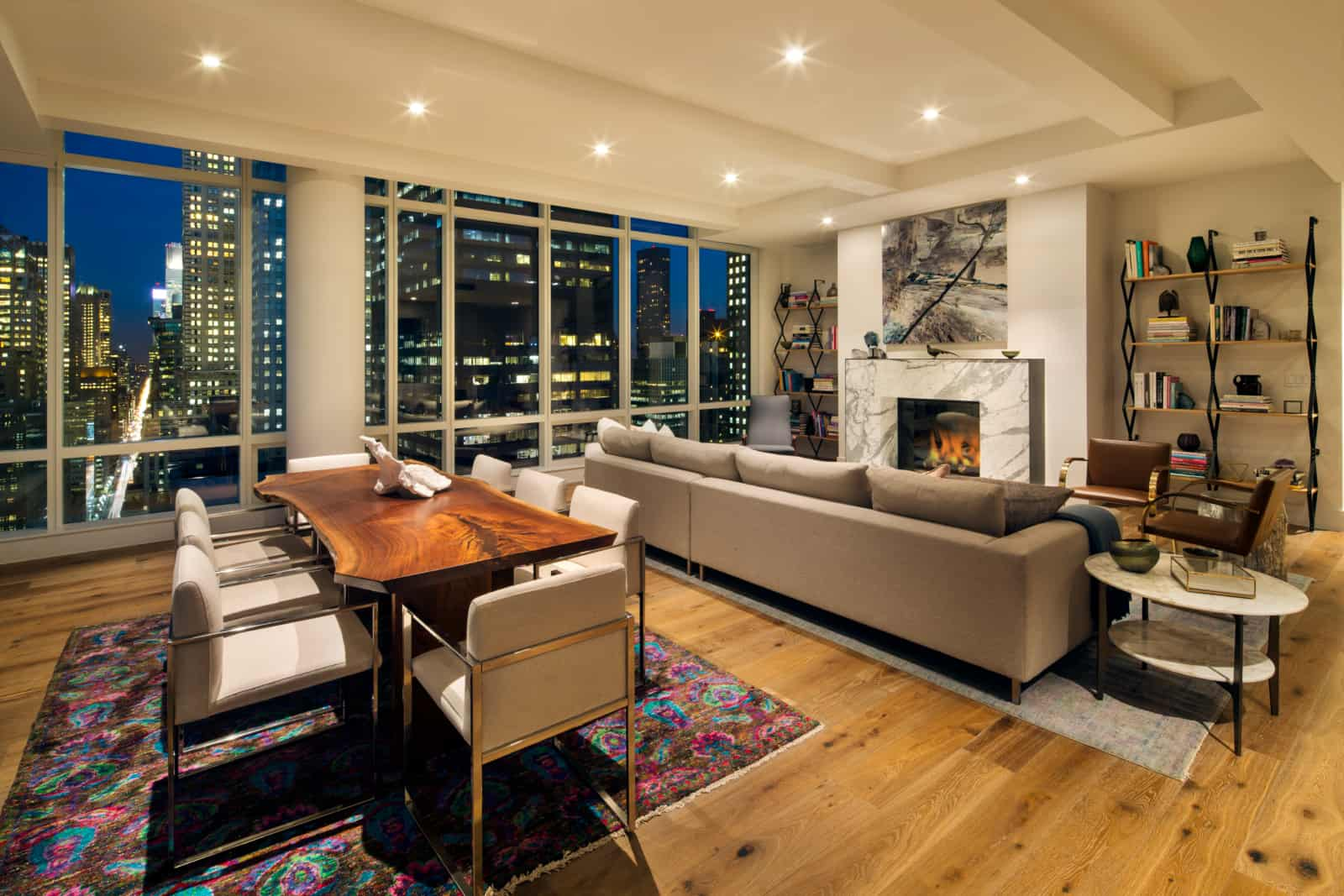 Large open plan apartment with living room area with fireplace, dining table, and large windows with city views.