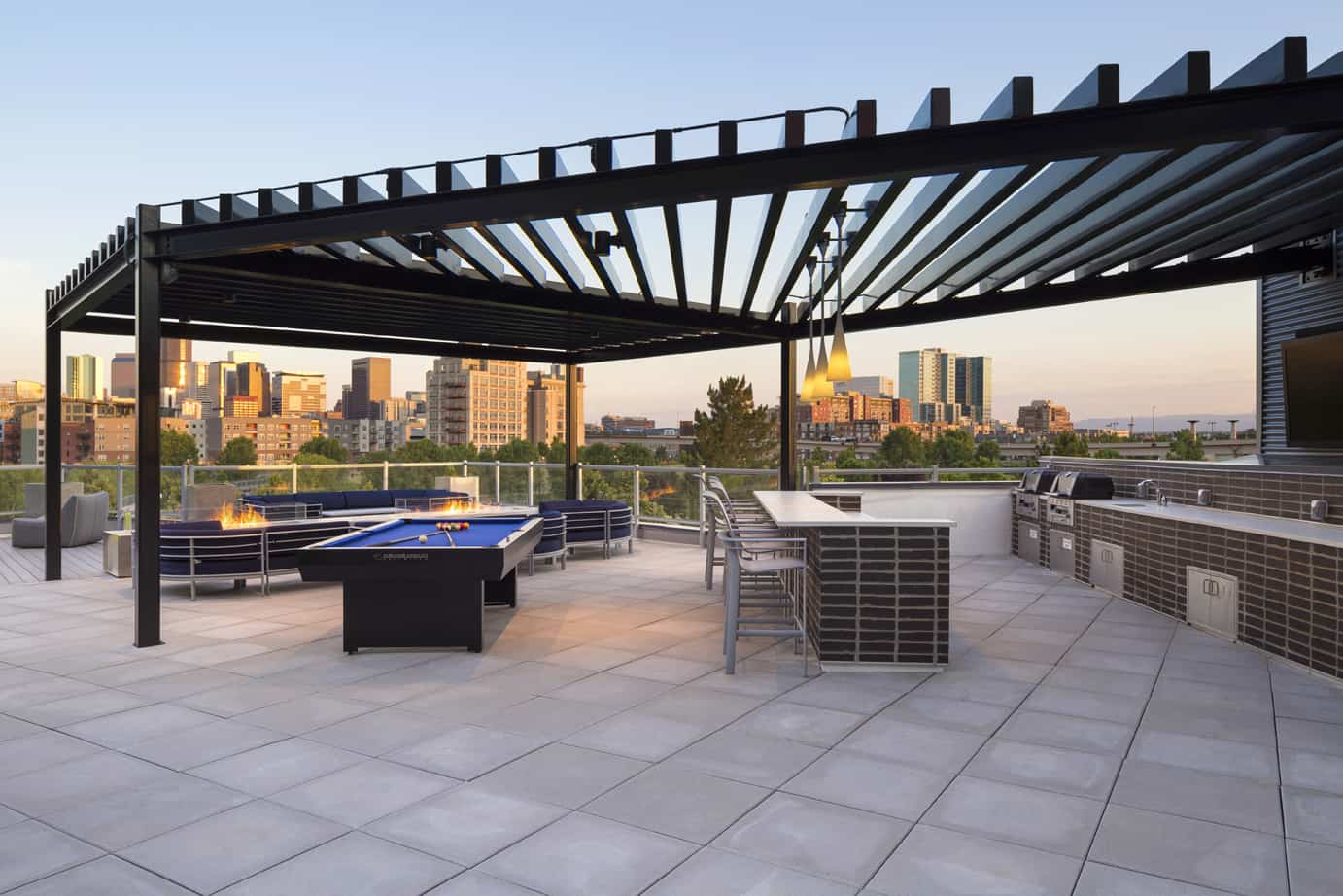 Roof top appointed with patio cover, barbeques, bar top height seating, pool table and couches with fire pit.