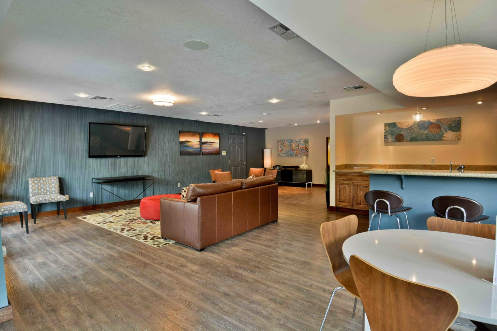 Interior of common area with couches, chairs, tables, TV, and kitchen area.