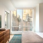 Modern apartment bedroom with city views out large window.