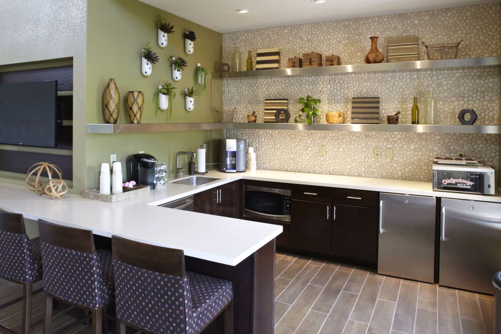 Interior of the common area kitchen with stainless steel appliances, cookie oven, and coffee maker.