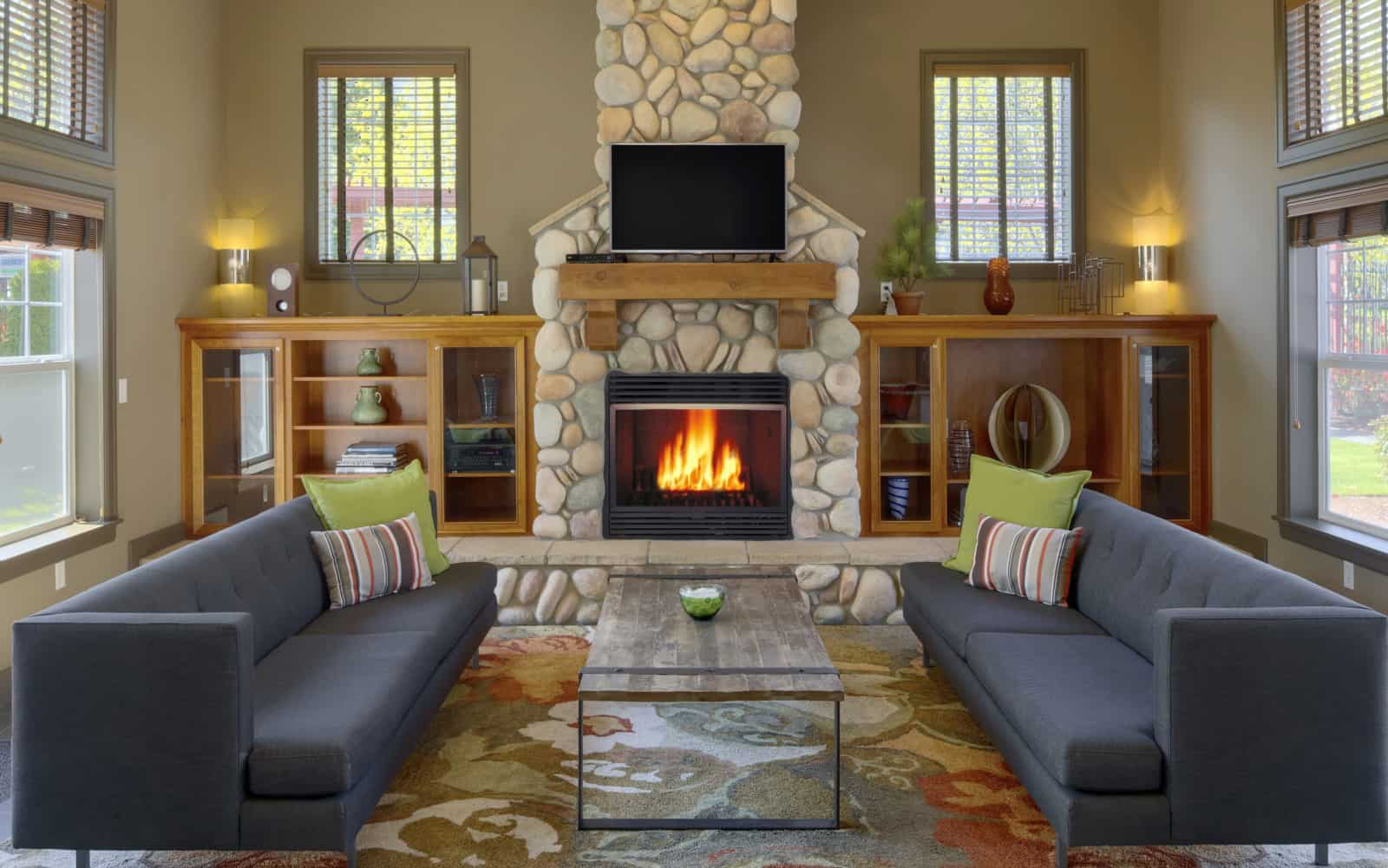 Interior of common area with stone fireplace, built-in shelves, couches, and coffee table.