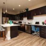 Open kitchen with center island, white counter tops and dark cabinets.