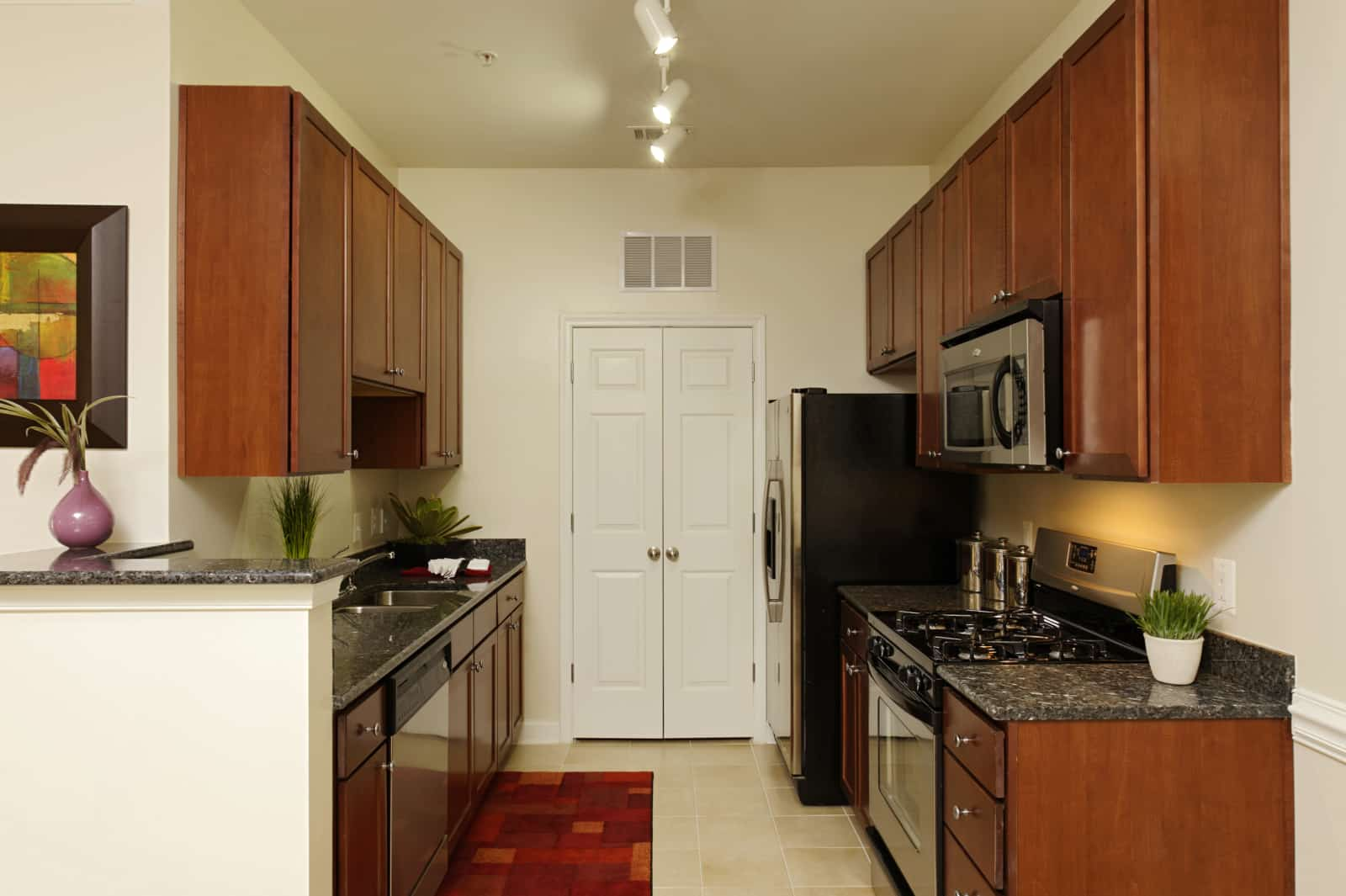 Interior of a galley kitchen with stainless steel appliances.