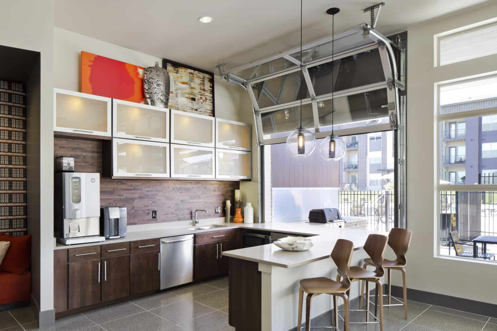 Interior of kitchen in the common area with view of the bbq grill through the window.