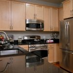 Kitchen with stainless steel appliances and black countertops.