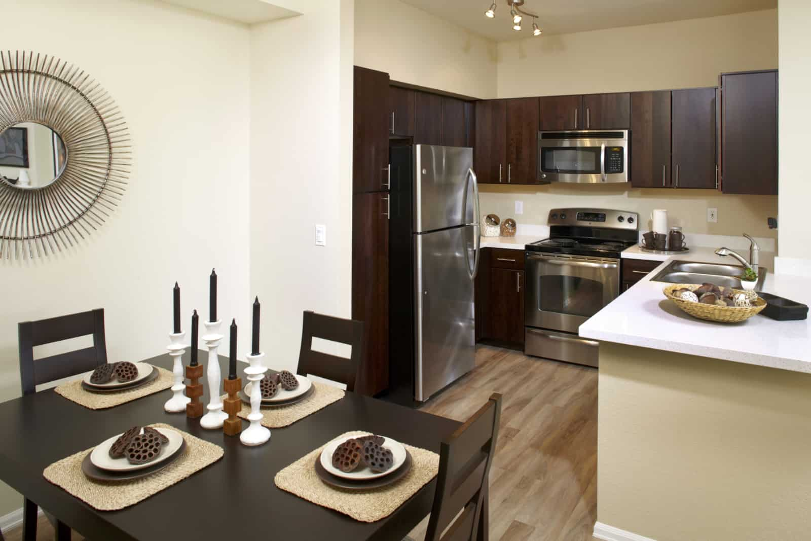 interior of a kitchen with stainless steel appliances, white countertop and a dining table and chairs in the foreground.