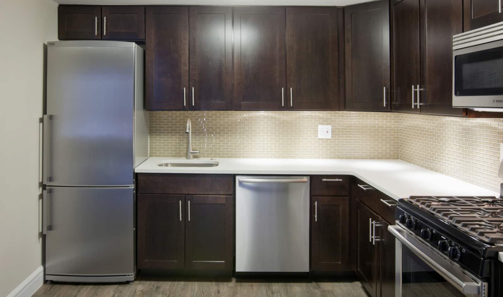 Interior of apartment kitchen with stainless steel appliances, white countertops and dark cabinets.