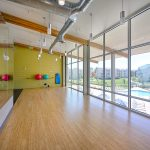 View of empty fitness room with bamboo floors and large windows.