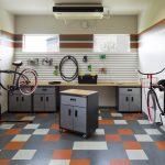 Interior of a bike repair room with workbench, tool cabinets, various tools and two bikes on stands.