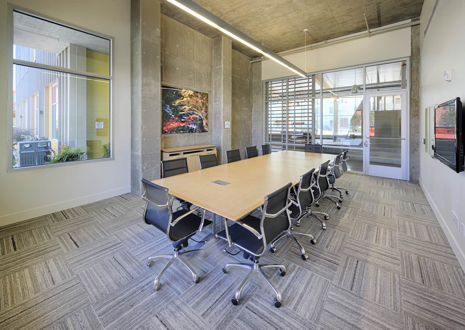 Conference room with a large table, chairs, white board and TV..