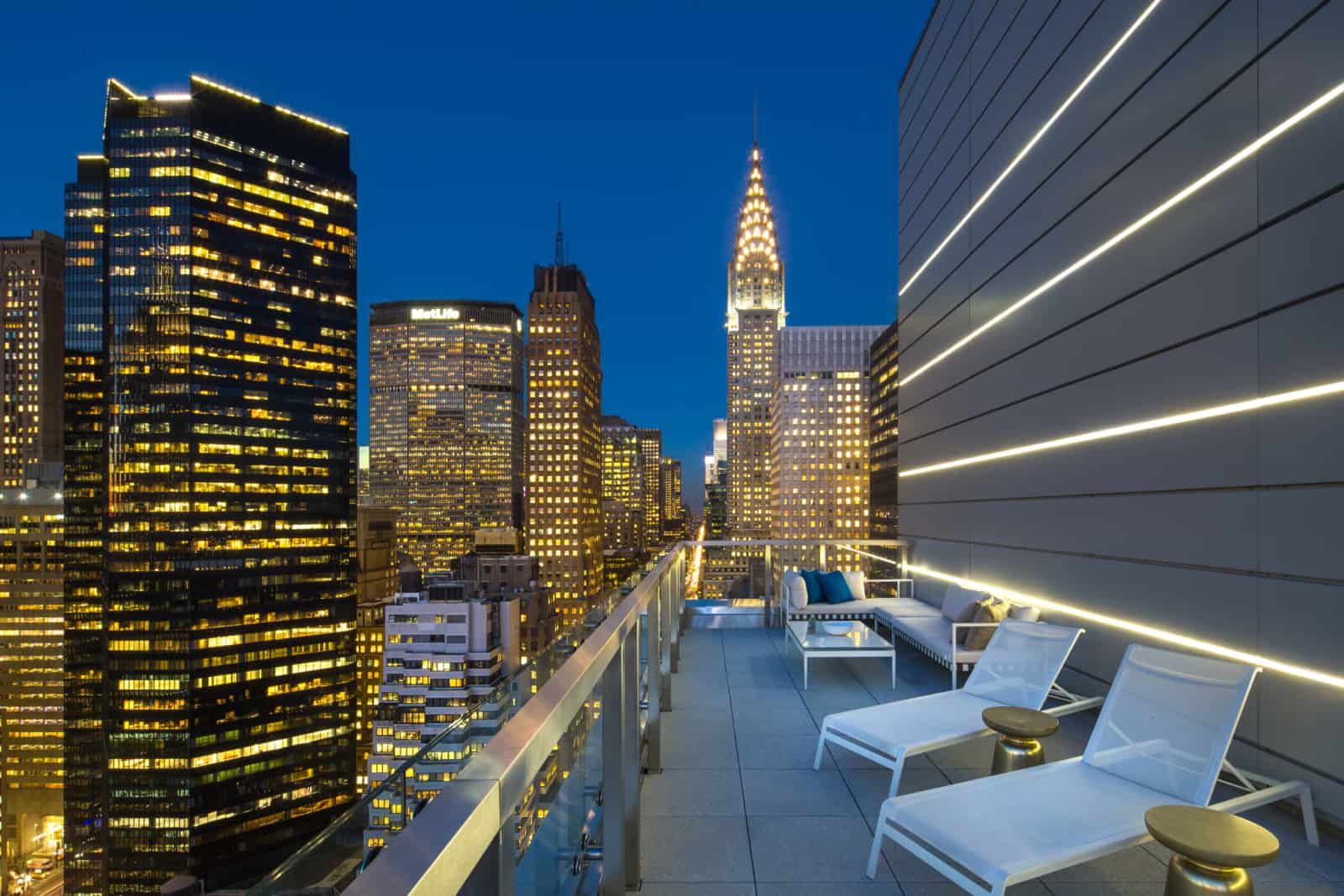 Exterior of large balcony with seating amidst downtown New York skyscrapers.