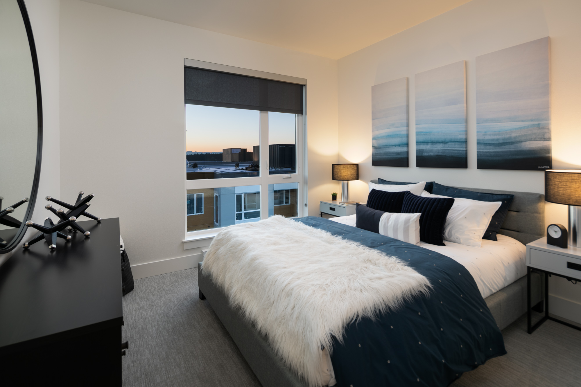 Interior of apartment bedroom with modern furnishings and large window