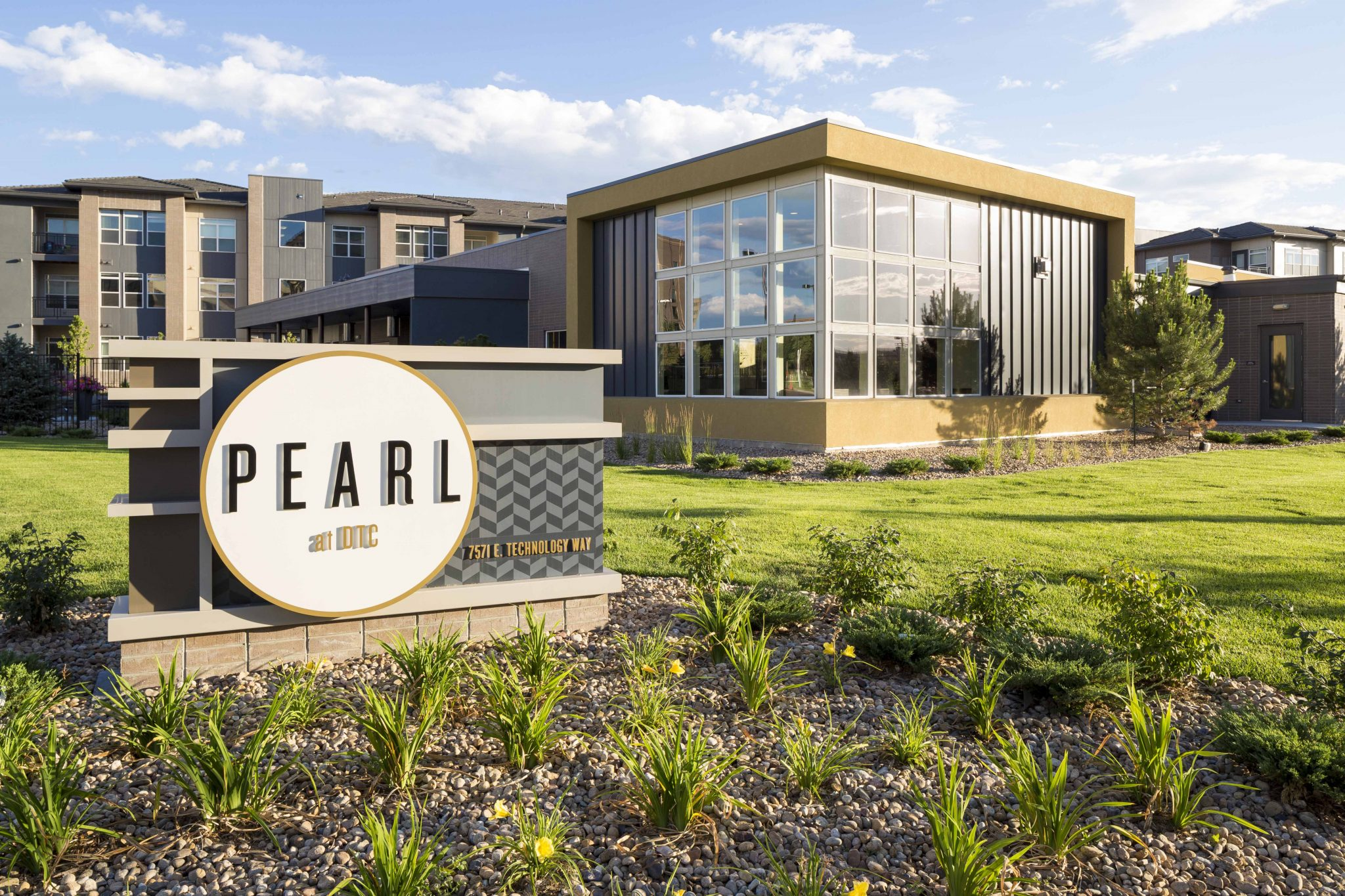 Exterior with sign for Pearl apartments with buildings in the background