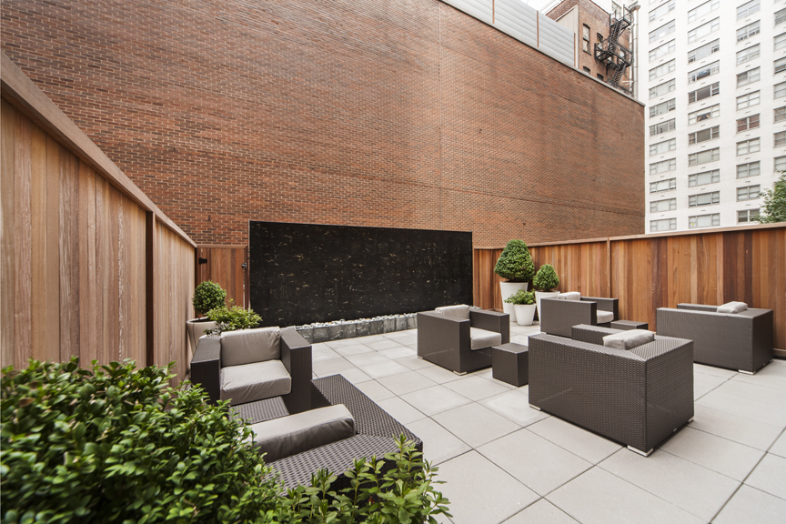 Exterior of outdoor courtyard with modern chairs, tables and a water feature in the background..