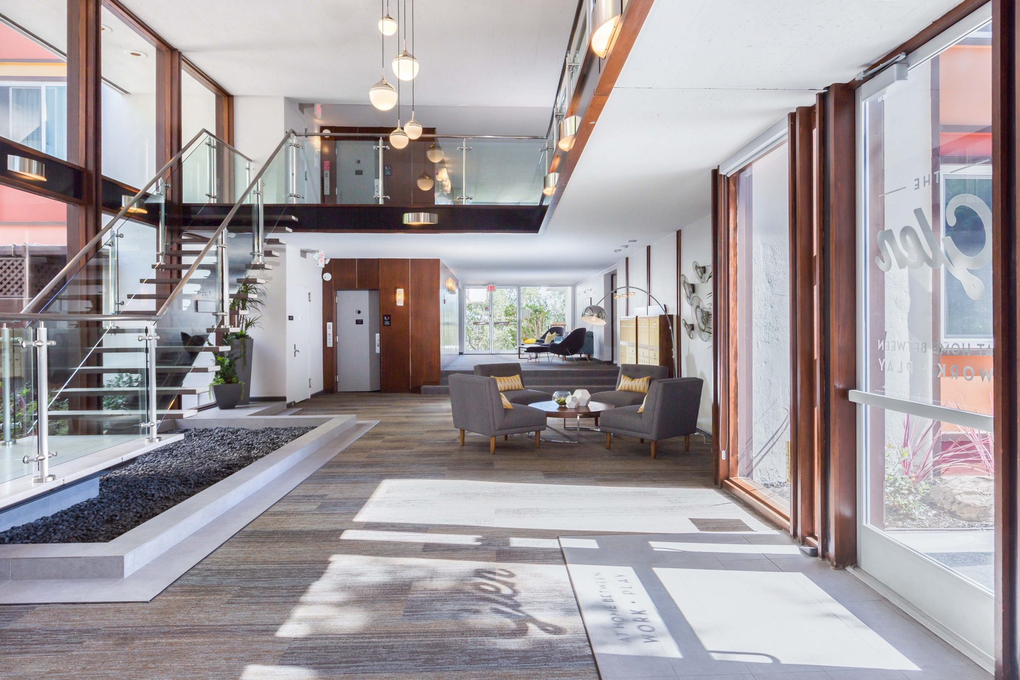 Interior of entrance to apartment complex with large floor-to-ceiling windows, glass stairway, and modern furniture