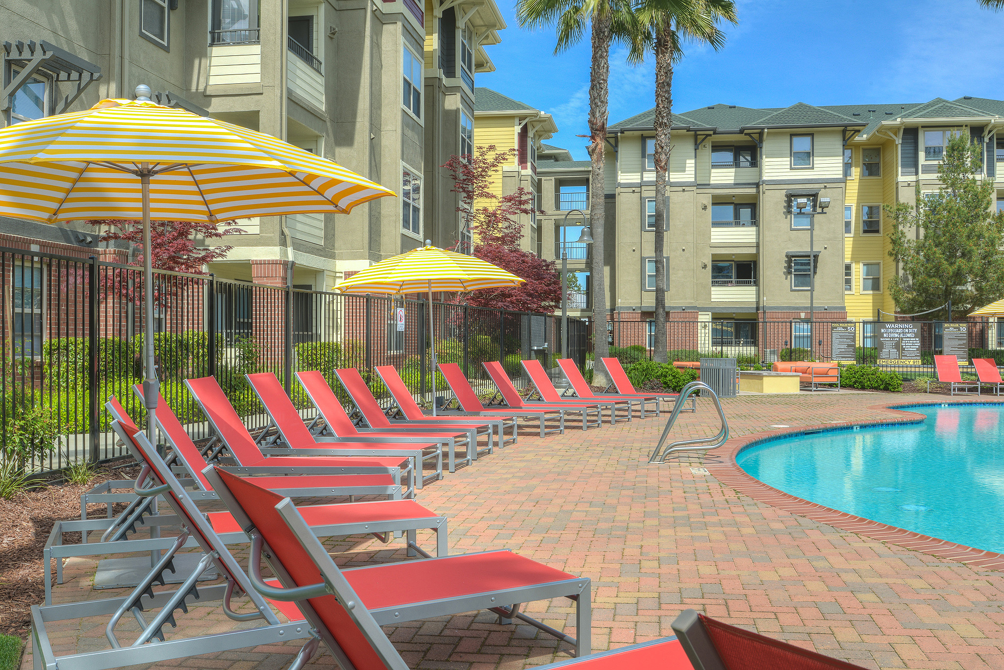 Exterior of pool with brick pool deck rimmed with lounge chairs with 4-story apartment buildings in background
