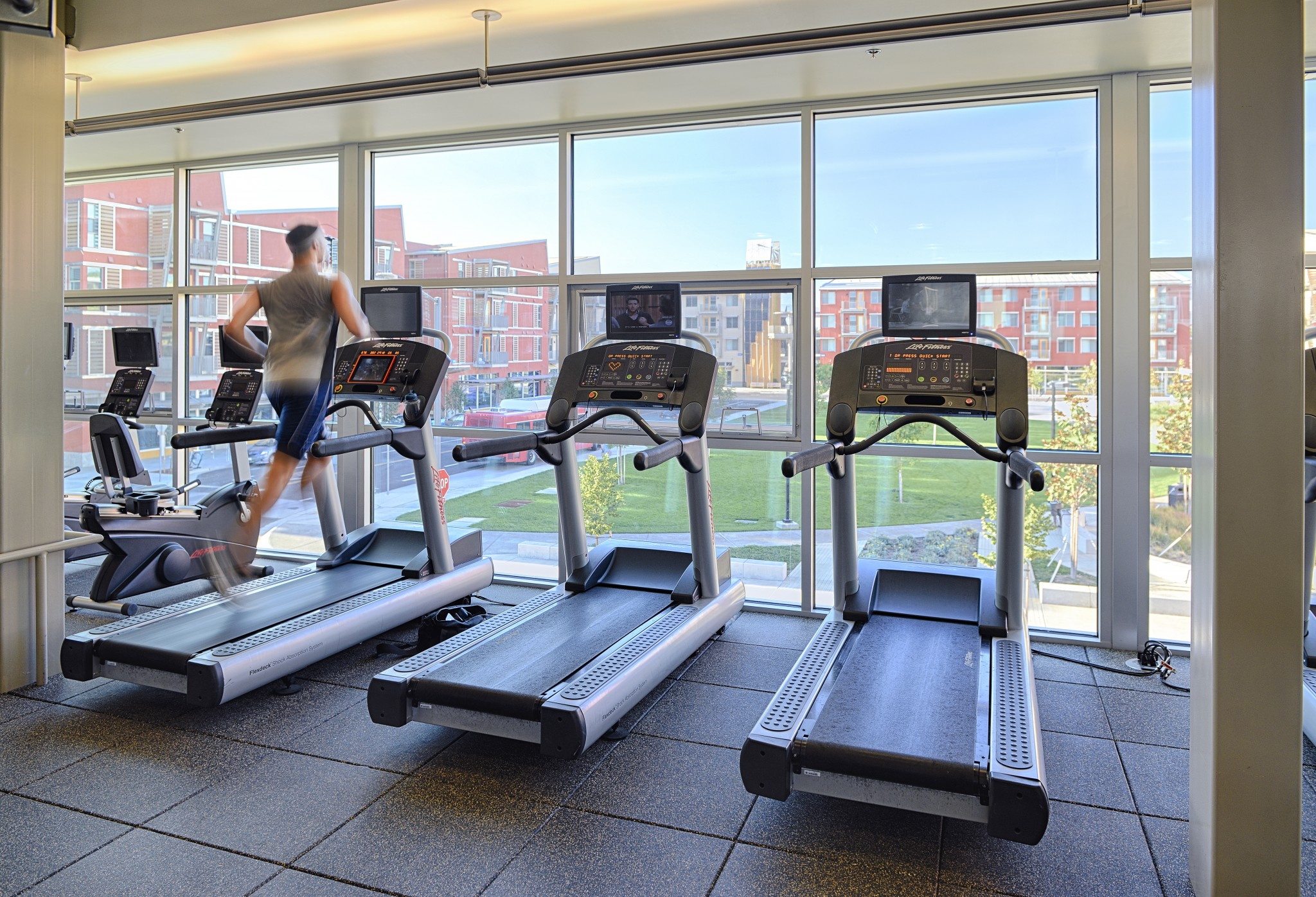 Treadmills in front of large windows with views of other apartment buildings across the way.