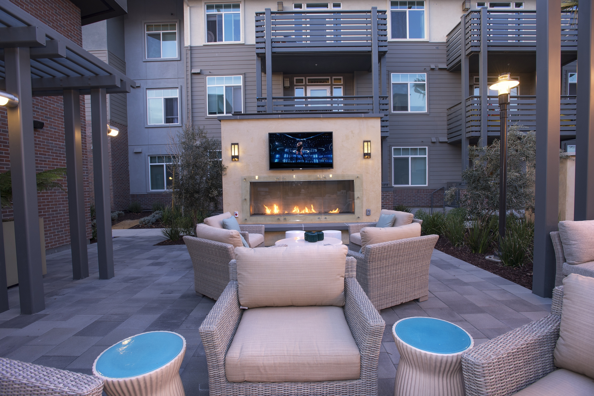 Exterior common area with seating, fireplace and large-screen television surrounded by apartment buildings