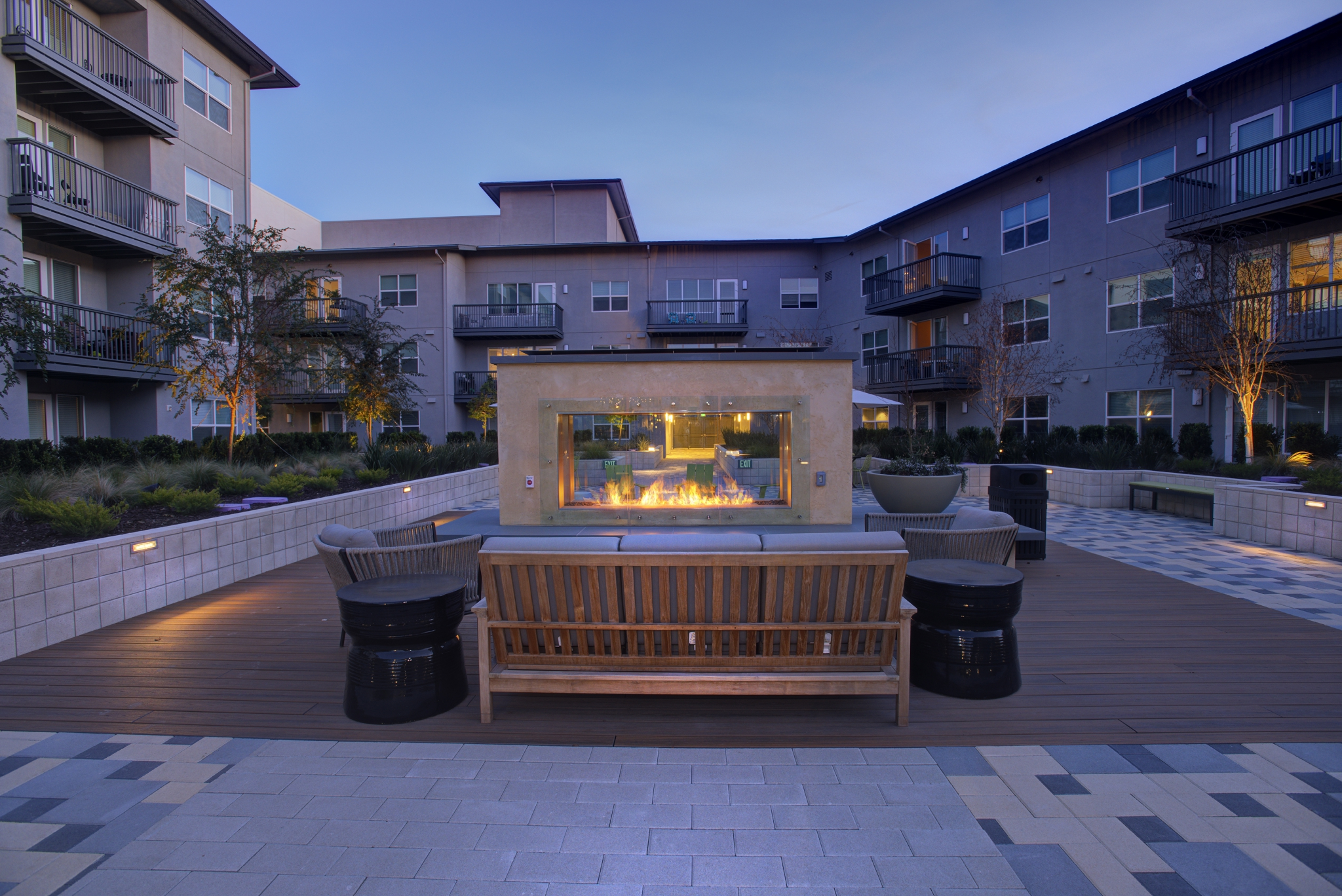 Exterior of courtyard with couches and fireplace surrounded by 3- and 4-story apartment building