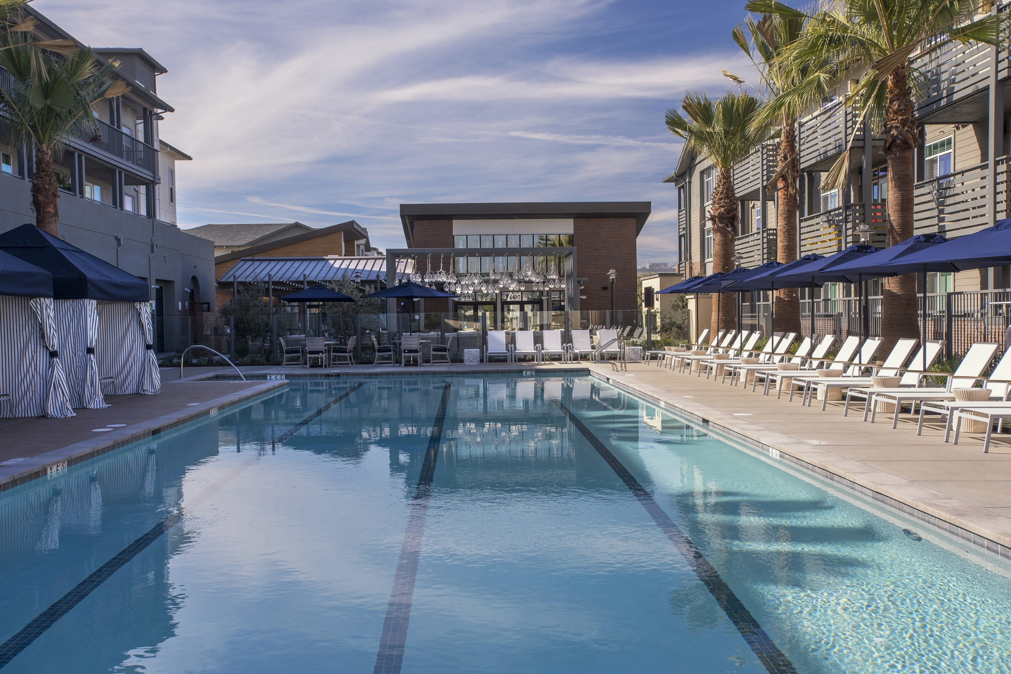 Exterior of pool with lounge chairs, umbrellas, and cabanas surrounded by apartment complex